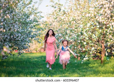 Mother and daughter in blooming garden enjoy the warm day