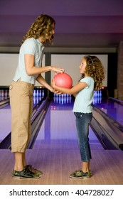 Mother and daughter in a bowling alley, holding a red bowling ball
