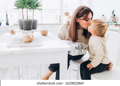 Mother and daughter in a bright kitchen. Homeliness. Joyful baby and his mom.