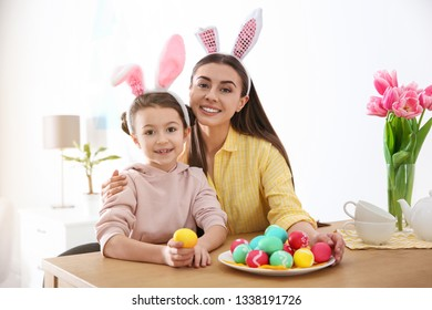 Mother and daughter with bunny ears headbands and painted Easter eggs at home