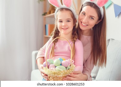 Mother and daughter in bunny ears together at home easter celebration sitting looking camera holding basket with eggs
