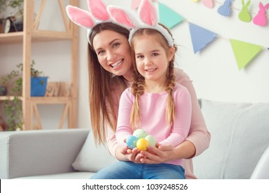 Mother and daughter in bunny ears together at home easter celebration sitting holding eggs looking camera