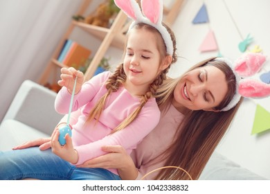 Mother and daughter in bunny ears together at home easter celebration sitting sticking ribbon to egg