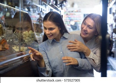 mother and daughter buying dark and white chocolate filled candies