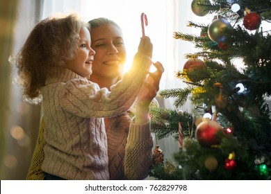 Mother and daughter celebrate Christmas in a decorated house with a Christmas tree