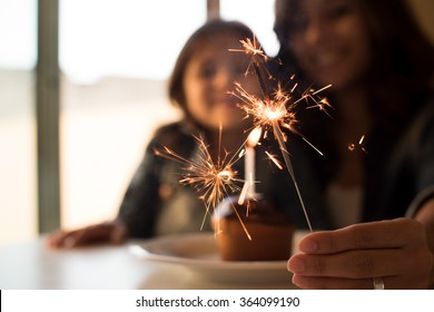 Mother and daughter celebrating birthday with cupcake- Focus on sparklers