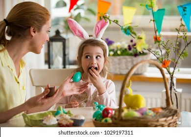 Mother and daughter celebrating Easter, eating chocolate eggs. Happy family holiday. Cute little girl with funny face in bunny ears laughing, smiling and having fun.