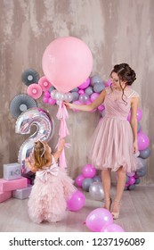 Mother with daughter celebrating family event both dressed in pink airy fancy dresses wearing golden crown on head.Studio shoot of lovely family with soft tender pastel colors