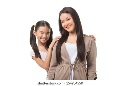 Mother and daughter. Cheerful mother and daughter standing close to each other and smiling while isolated on white