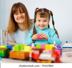 Mother and daughter cheerfully playing with toys on blue