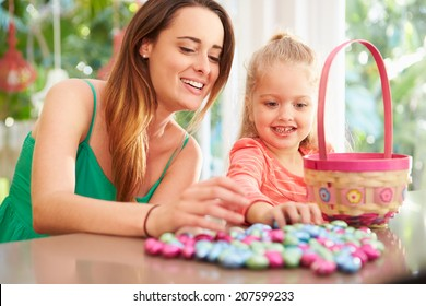 Mother And Daughter With Chocolate Easter Eggs And Basket