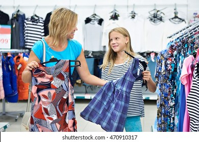Mother with daughter choosing a dress in clothing store