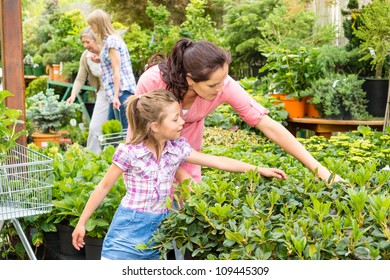 Mother and daughter choosing flowers at garden center shop