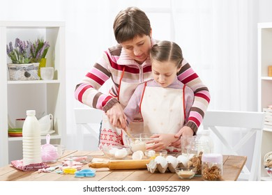 Mother and daughter cook at home. Making cookies, kitchen interior, healthy food concept