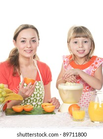 Mother and daughter are cooking an orange juice