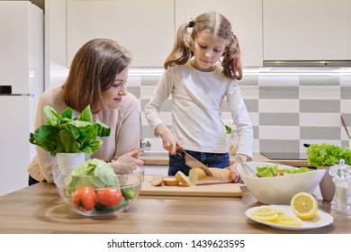 Mother and daughter cooking together in the kitchen at home, girl cutting bread.