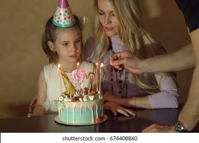 mother and daughter countIng candles on a birthday cake. little girl in a festive hat at a children's party.