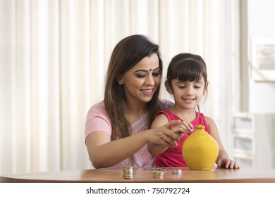 Mother and daughter counting and depositing coins into piggy bank