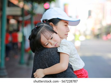 Mother and daughter cuddling, Beautiful little girl hugging her mother outdoor.