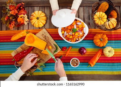 Mother and daughter cutting pumpkin, onion and carrot, cooking soup for autumn meal. Healthy fall vegetables for Halloween season lunch. Squash cut on wooden table in sunny kitchen. Flat lay. Top view
