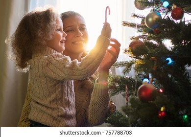 Mother and daughter decorate a Christmas tree against the window with a setting sun and bright sunlight