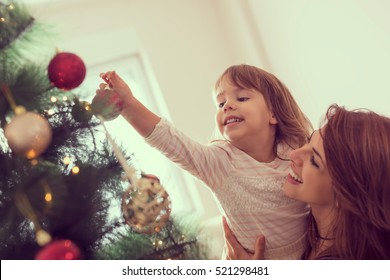 Mother and daughter decorating Christmas tree and having fun. Focus on the daughter