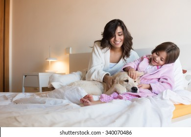 Mother and daughter with dog in bed