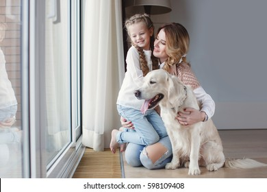 Mother and daughter with dog at home. Portrait of happy girl with dog lying on rug while mother relaxing at home. family with pet