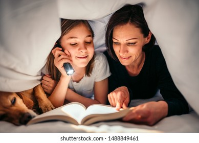 Mother, daughter and dog laying on the bed under blanket holding flashlight and reading book late at night