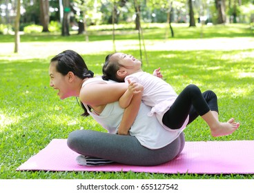 Mother and daughter doing exercise in the garden