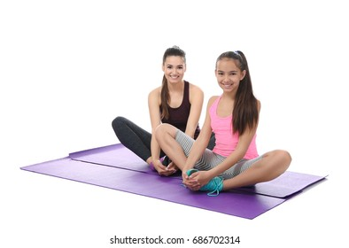 Mother and daughter doing exercise on white background