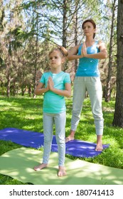 Mother and daughter doing exercise outdoors - mother teaching her daughter how to do exercises