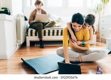 Mother and daughter doing exercises on the floor in living room while Father sitting on couch and working on laptop. Time break. Using tablet
