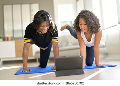 Mother and daughter doing fitness exercices at home