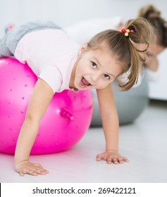 Mother with daughter doing gymnastic exercises with balls