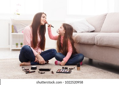 Mother and daughter doing makeup sitting on the floor in the bedroom. Mothers Day, relationship, motherhood, joint activities and interests, trust, support, caress, maternal warmth, caring concept