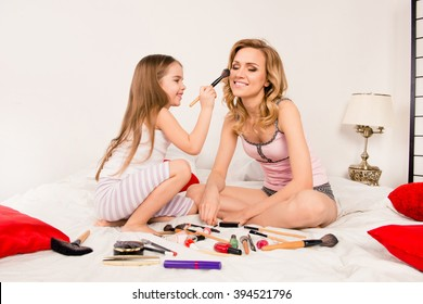 Mother and daughter doing  makeup sitting on the bed in the bedroom