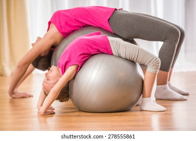 Mother and daughter doing physical exercises on fitness ball at home.