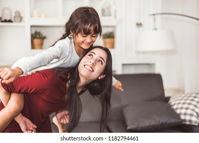 Mother and daughter doing piggyback in funny gesture emotion at home. Young sister playing with girl in good relationship lifestyles relaxation. Happy family and home sweet home theme concept