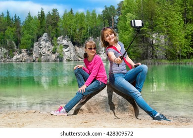 Mother and daughter are doing Selfe on the shore of Piskovna lake. National Park of Adrspach-Teplice rocks. Rock Town. Czech Republic.