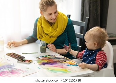 mother and daughter doing watercolor painting - girl looking at her dirty hand