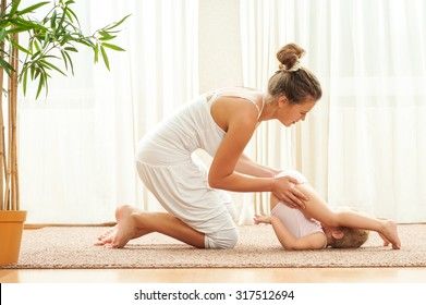 Mother and daughter doing yoga  exercise home. Mother and baby gymnastics.
