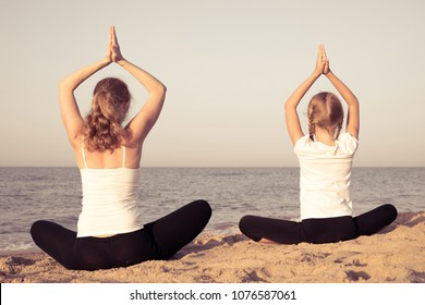 Mother and daughter doing yoga exercises  on the beach at the day time. People having fun outdoors. Concept of summer vacation and friendly family.