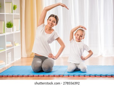Mother and daughter doing yoga exercises on mat at home.