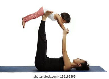 Mother and daughter doing yoga together in a fitness studio