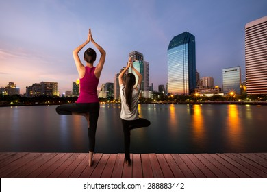 Mother and daughter doing yoga tree pose at city