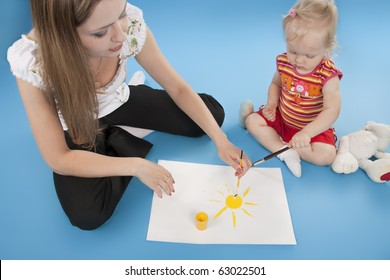 Mother and the daughter draw paints the sun.  Isolated  blue.