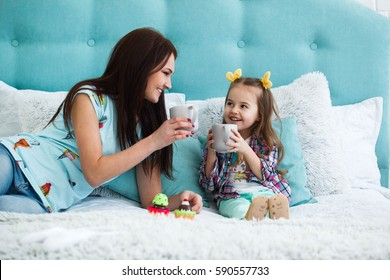 Mother and daughter drink tea from large mugs sitting on the bed
