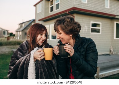 Mother and Daughter Drinking from Coffee Cups at Sunset at the Beach looking at sunset laughing and smiling with each other