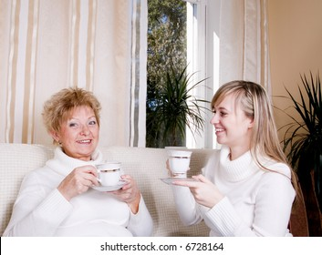 Mother and daughter drinking coffee together